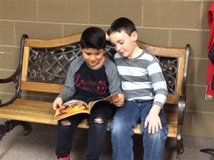 Two boys sitting on a wooden bench and reading a book.